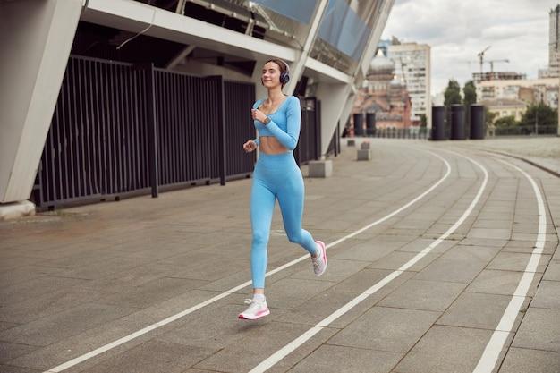 Молодая подтянутая дама занимается фитнесом и бегает трусцой в городе
