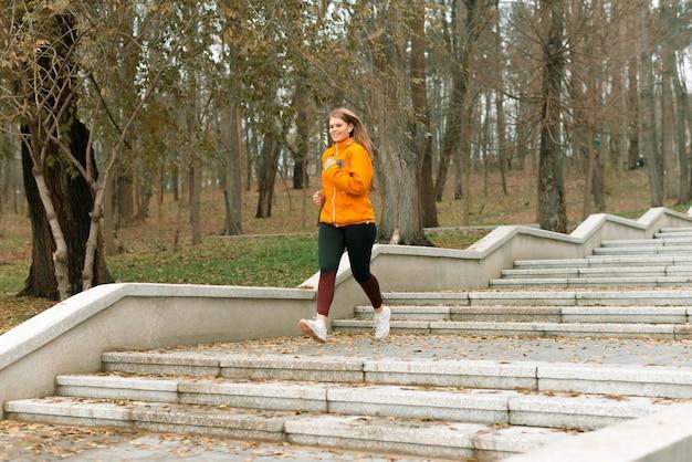 젊은 맞는 아가씨가 아침에 공원에서 계단을 내려 가고 있습니다.