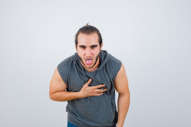 Young fit male feeling nauseated in sleeveless hoodie  and looking painful. front view.