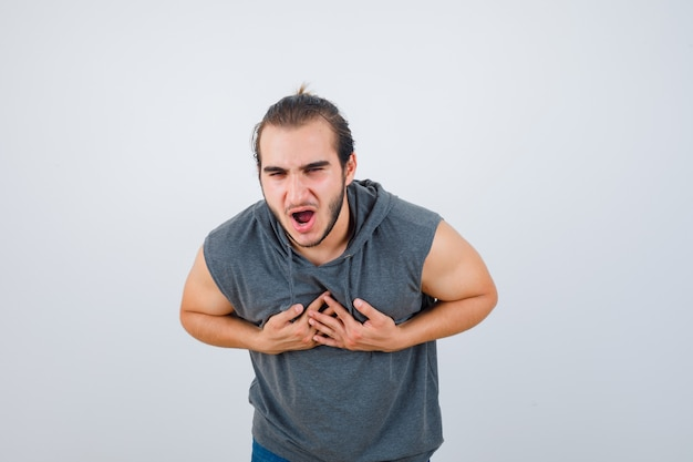 Young fit male feeling nauseated in sleeveless hoodie  and looking unwell , front view.