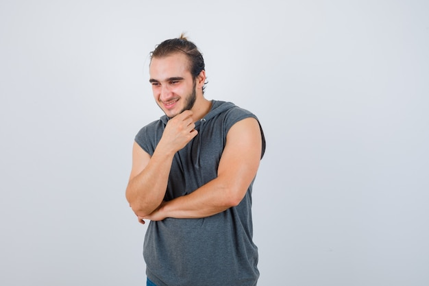 Young fit male keeping hand under chin in sleeveless hoodie  and looking blissful , front view.