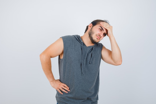 Young fit male keeping hand on forehead in sleeveless hoodie  and looking painful , front view.