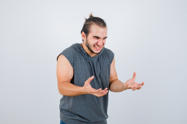 Young fit male keeping hands in aggressive manner in sleeveless hoodie   and looking angry. front view.