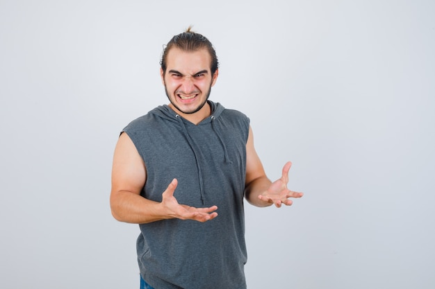 Young fit male keeping hands in aggressive manner in sleeveless hoodie  and looking anxious. front view.
