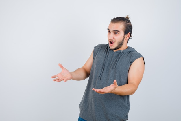 Young fit male making receiving gesture in sleeveless hoodie and looking shocked. front view.