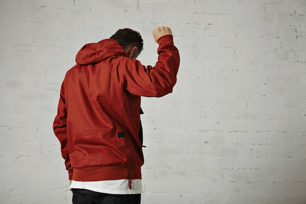 A young fit male model in brick red sports jacket holds his fist up in the air portrait from the back isolated on white