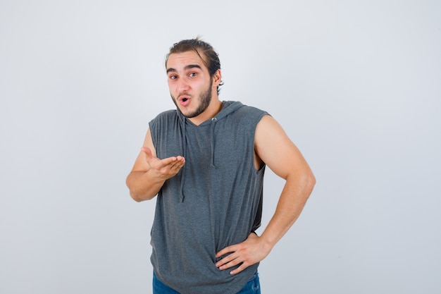 ノースリーブのベストで手のひらを広げ、ショックを受けているように見えながら、腰に手を当ててポーズをとる若いフィットの男性。正面図。