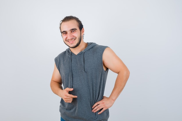 Young fit male posing with hand on waist in sleeveless hoodie  and looking cheerful. front view.