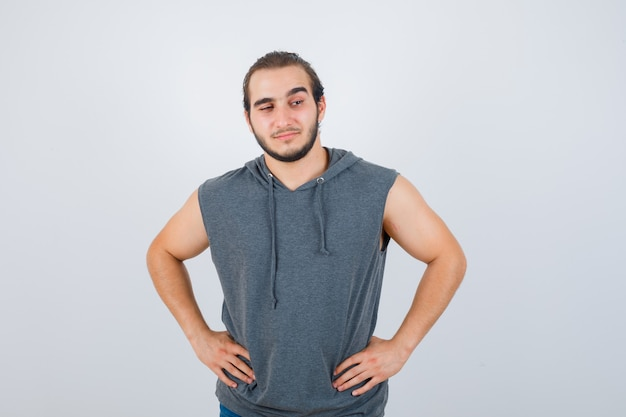Young fit male posing with hands on waist in sleeveless hoodie  and looking blissful. front view.