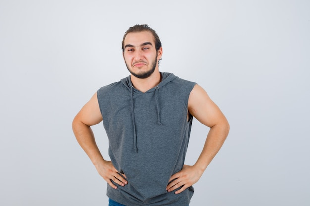 Young fit male posing with hands on waist in sleeveless hoodie  and looking cheerful , front view.