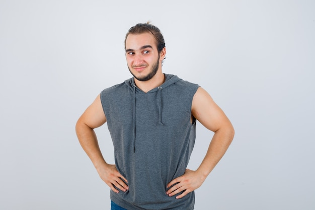 Young fit male posing with hands on waist in sleeveless hoodie  and looking cheerful. front view.