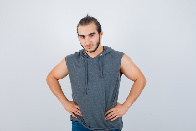 Young fit male posing with hands on waist in sleeveless hoodie  and looking confident , front view.