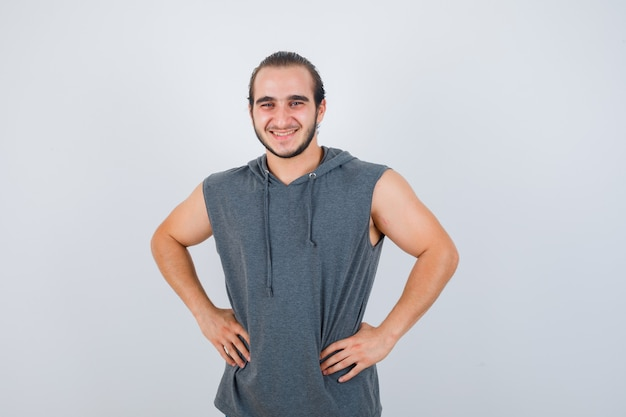 Young fit male posing with hands on waist in sleeveless hoodie  and looking merry , front view.