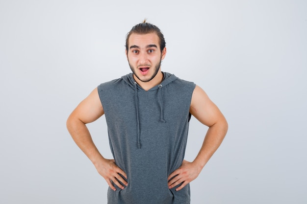 Young fit male posing with hands on waist in sleeveless hoodie  and looking shocked , front view.