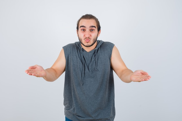 Young fit male pretending to hold something in sleeveless hoodie  and looking hesitant. front view.