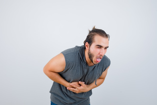 Young fit male in sleeveless hoodie  feeling nauseated and looking painful , front view.