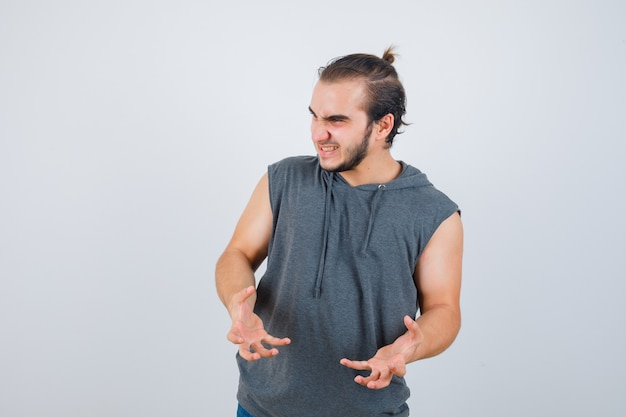 Young fit male in sleeveless hoodie  keeping hands in aggressive manner and looking annoyed , front view.