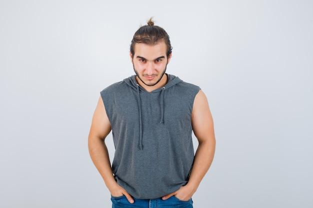 Giovane maschio in forma in felpa con cappuccio senza maniche tenendo le mani in tasca e guardando fiducioso, vista frontale.