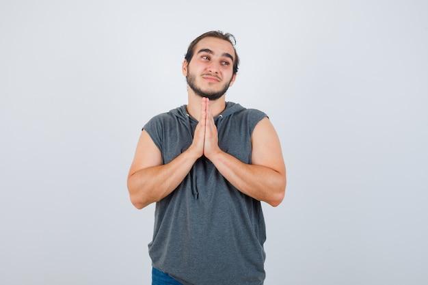 Giovane maschio in forma in felpa con cappuccio senza maniche mantenendo le mani nel gesto di preghiera e guardando speranzoso, vista frontale.