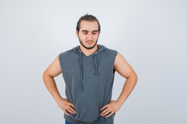 Young fit male in sleeveless hoodie  posing with hands on waist and looking pensive , front view.