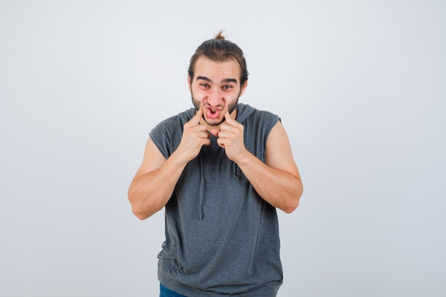 Young fit male in sleeveless hoodie   pressing cheeks with fingers and looking glad , front view.