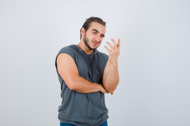 Young fit male in sleeveless hoodie  raising hand in questioning manner and looking cheerful , front view.