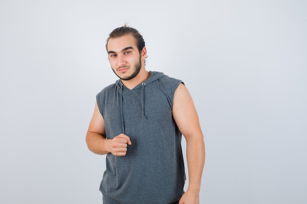 Young fit male in sleeveless hoodie  showing clenched fist and looking confident , front view.