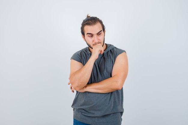 Young fit male in sleeveless hoodie  standing in thinking pose and looking pensive , front view.