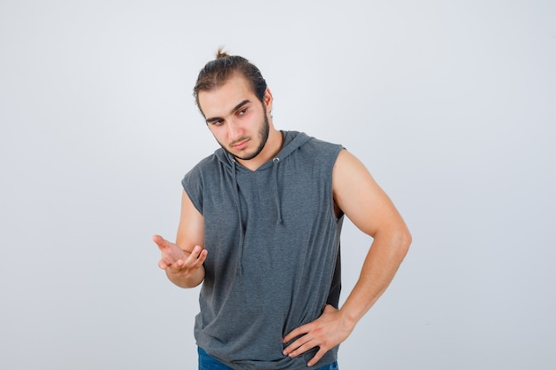Young fit male in sleeveless hoodie  streching hand towards camera and looking pensive , front view.