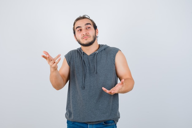Young fit male in sleeveless hoodie  stretching hand in questioning manner and looking pensive , front view.