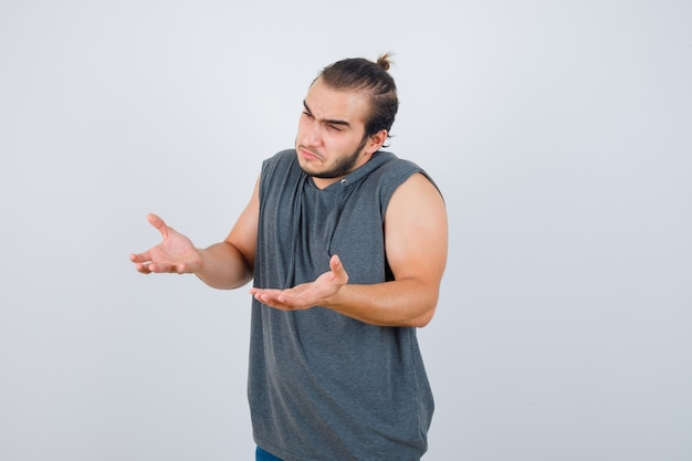 Young fit male spreading palms in questioning manner in sleeveless hoodie  and looking pensive , front view.