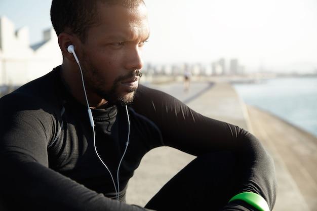 音楽を聴いてビーチで若いフィット男