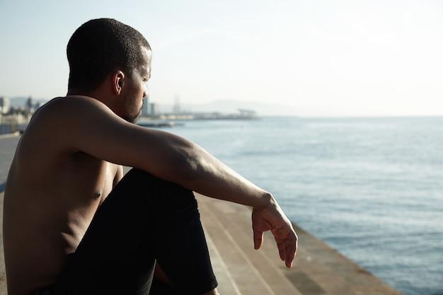 Giovane uomo in forma in spiaggia ammirando il paesaggio