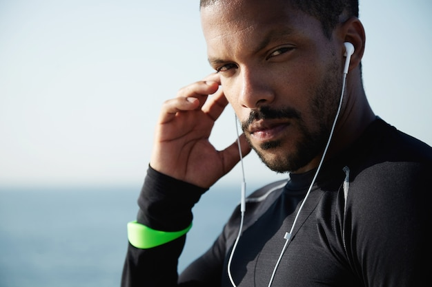 Giovane uomo in forma in spiaggia ascoltando musica