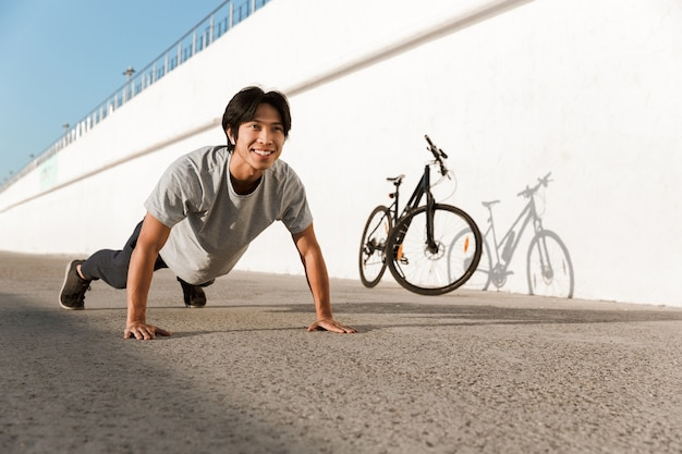 Young fit man bicyclist working out oudoors, doing push-ups