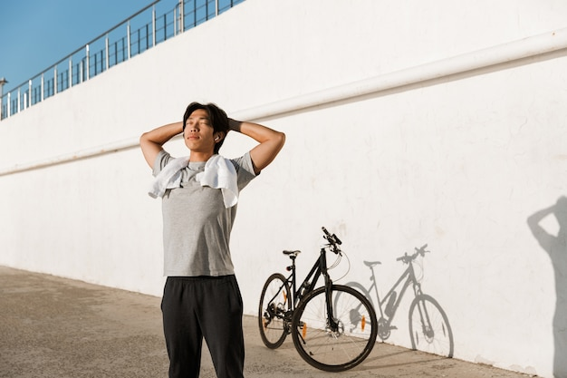Young fit man bicyclist working out oudoors, resting