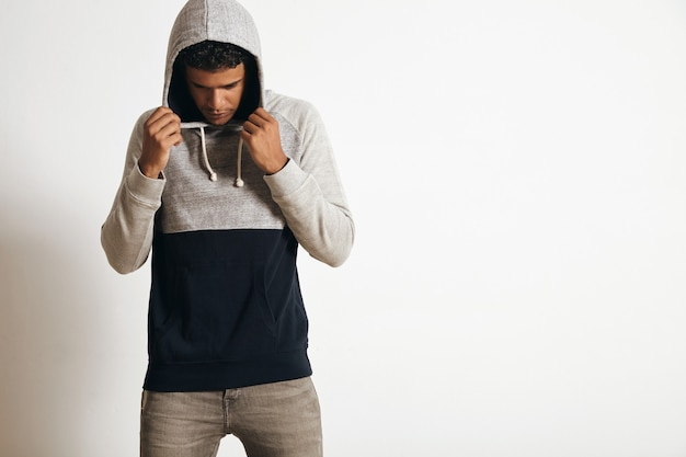 Young and fit man in blank grey black hoodie sweater posing in front of white wall, looking down