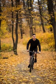 秋の公園で晴れた日に自転車に乗る時に若い男に合う