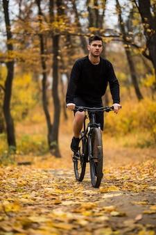 Молодой человек подходит во время езды на велосипеде в солнечный день в осеннем парке