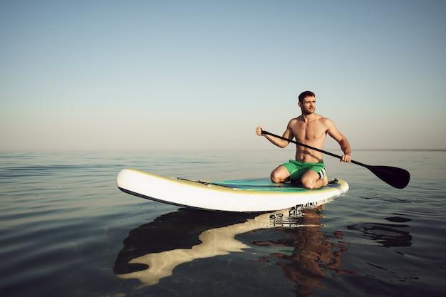 Молодой здоровый человек на доске с веслом, плавающей на озере