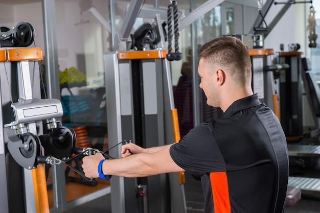 フィットネスセンターのジムルームでローイングマシンでトレーニングする若いフィット男