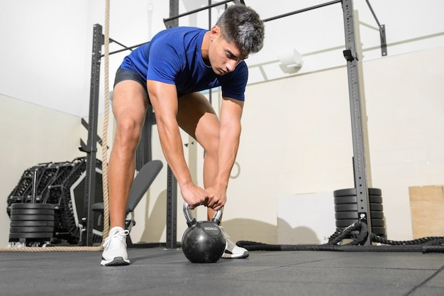 Young fit man training with kettlebells
