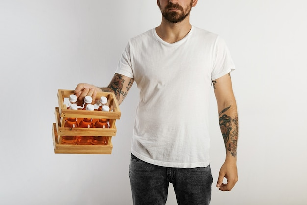 A young fit model with tattoos and beard holding a sixpack of unlabeled orange drinks isolated on white