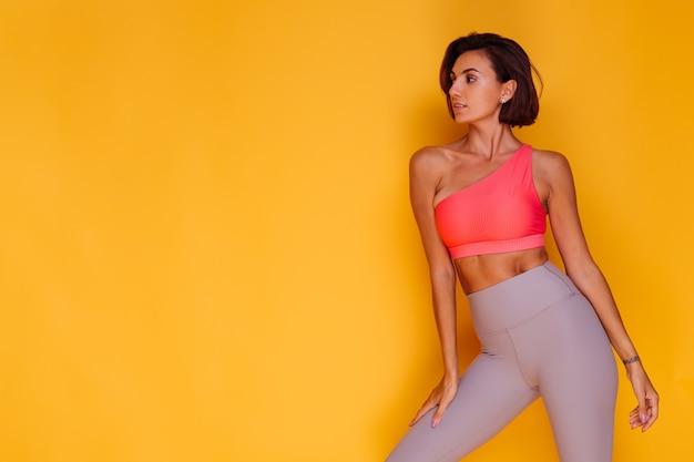 Молодая подтянутая довольно сильная женщина, одетая в спортивную одежду, стильный топ и леггинсы, позирует у желтой стены
