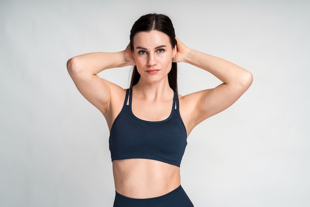 彼女の腕を彼女の頭に入れ、白い空白の壁に対してポーズをとる黒いスポーツ服を着た長いブルネットの髪を持つ若いフィットのきれいな女性。ボディービルとスポーツのコンセプト