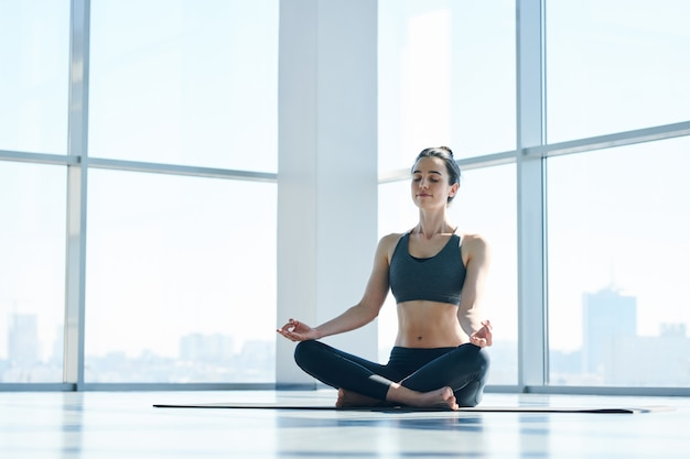 Young fit serene woman in black activewear sitting in pose of lotus on the floor, keeping balance and relaxing