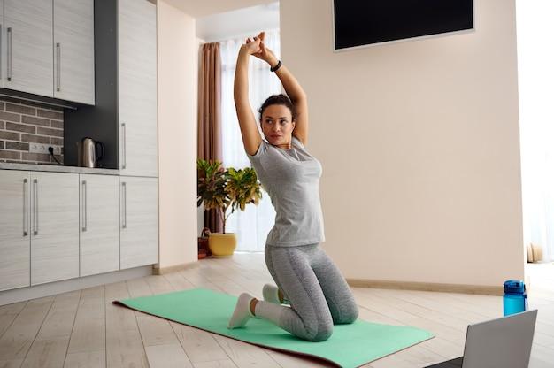 젊은 맞는 슬림 여성 피트 니스 매트에 서있는 그녀의 몸을 스트레칭. 집에서 운동하는 여자