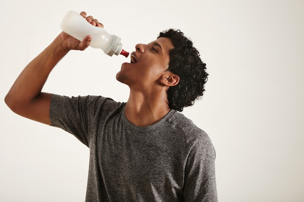 Young fit smiling black man drinking water from a sports bottle, mouth wide open, isolated on white