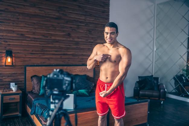 彼の強い体を示す赤いショートパンツで若いフィットスポーツvlogger