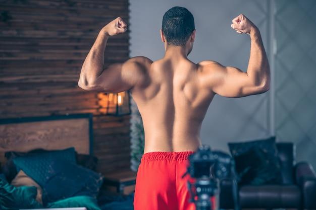 彼の強い肩を示す赤いショートパンツの若いフィットスポーツvlogger